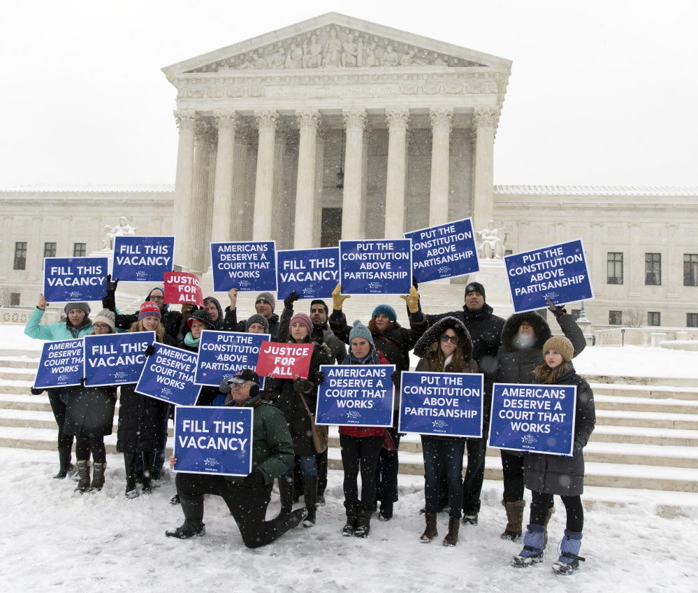"A group with ""People for the American Way"" from Washington gather with signs in front of the U.S. Supreme Court on Monday as they call for Congress to give fair consideration to any nomination put forth by President Obama to fill the seat of Antonin Scalia."