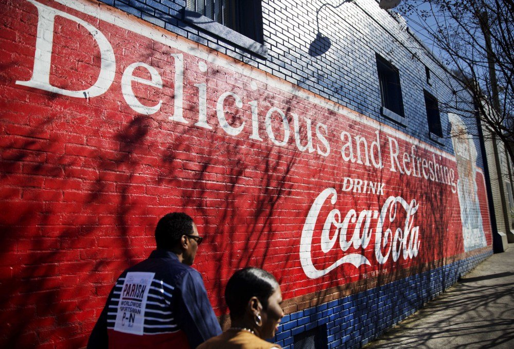 A mural advertising Coca-Cola decorates the side of a building as pedestrians pass Thursday in Atlanta. Coke and Pepsi are trying to rehabilitate soda's cheap image in an effort to fetch higher prices.