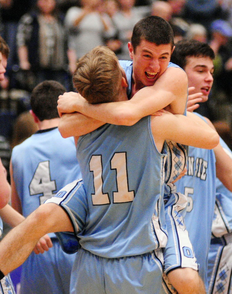 Oceanside's Riley Sprague gets hugged by teammate Josh Luttrell as the Mariners celebrate a win over Medomak Valley in the Class A North championship game Friday at the Augusta Civic Center.