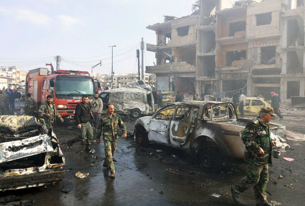 Syrian citizens gather at the scene of multiple explosions in the Sayyida Zeinab suburb outside Damascus, Syria, on Sunday.