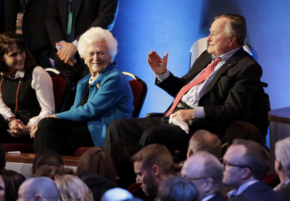 Former President George H. W. Bush, right, and his wife, Barbara Bush are greeted before Thursday night's Republican presidential debate at the University of Houston. Their son Jeb Bush dropped out of the Republican race last weekend.