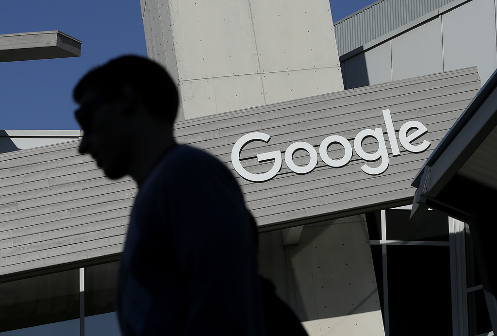 FILE - In this Nov. 12, 2015, file photo, a man walks past a building on the Google campus in Mountain View, Calif. The Associated Oress