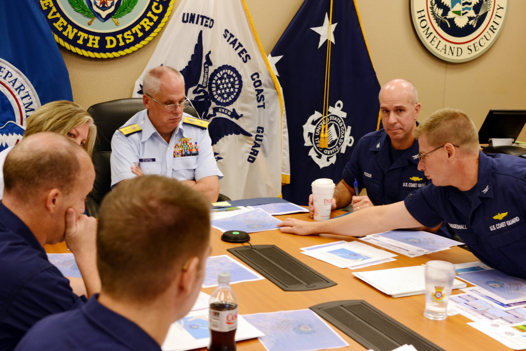In this Oct. 3, 2015, file photo, Rear Adm. Scott Buschman, commander of the Coast Guard 7th District, receives an update brief for the missing cargo ship El Faro at the Coast Guard 7th District in Miami. A series of U.S. Coast Guard hearings starting Tuesday, Feb. 16, 2016, will seek answers about why the freighter El Faro sank near the Bahamas last fall, killing all crew members in the worst U.S. commercial maritime disaster in decades.