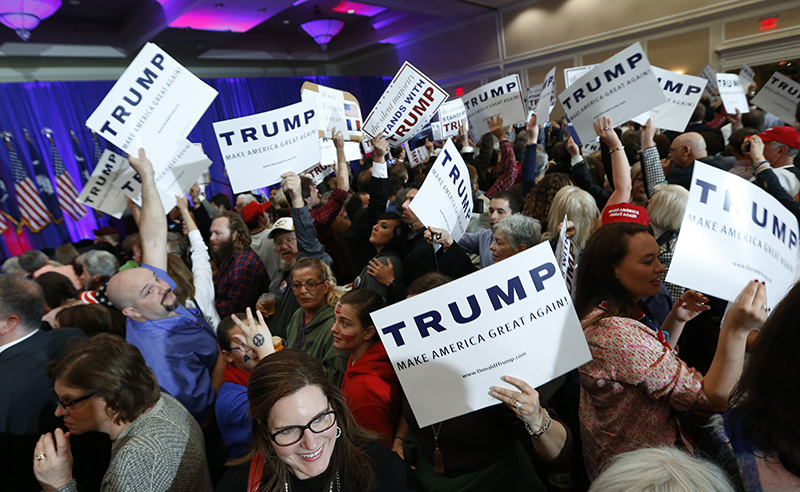 Supporters for Republican presidential candidate Donald Trump hold signs during a South Carolina Republican primary night event. in Spartanburg, S.C.