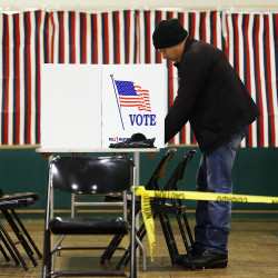A voter marks his ballot in the first-in-the-nation presidential primary, Tuesday in Nashua, N.H. The Associated Press