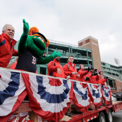 The Boston Red Sox new mascot Tessie the Green Monster rides on the back of a truck with team ambassadors leading the team's equipment truck as it departs Fenway Park in Boston on Wednesday en route to the team's spring training baseball facility in Fort Myers, Fla. Boston pitchers and catchers will hold their first official workout on Feb. 19. The full team will have its first official workout on Feb. 24.