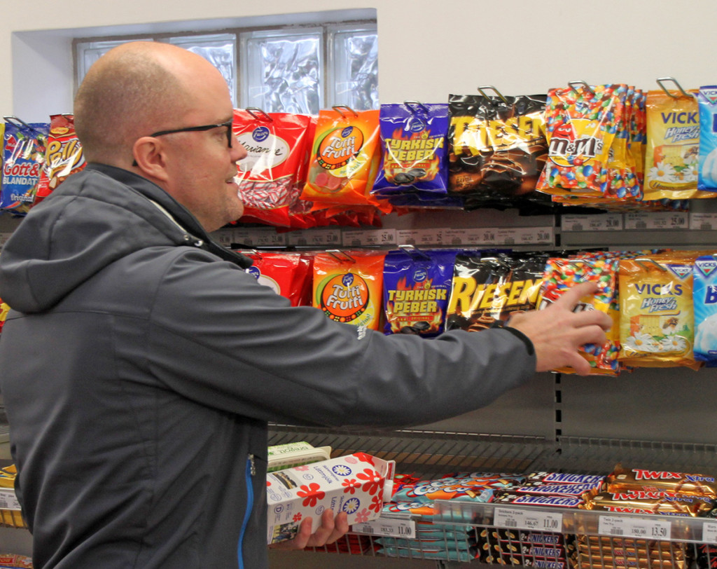 "Customer Raymond Arvidsson takes sweets from the display at the unstaffed store in the village of Viken. Robert Ilijason, who developed the unstaffed concept, says, ""It is incredible that no one has thought of this before."" The Associated Press"