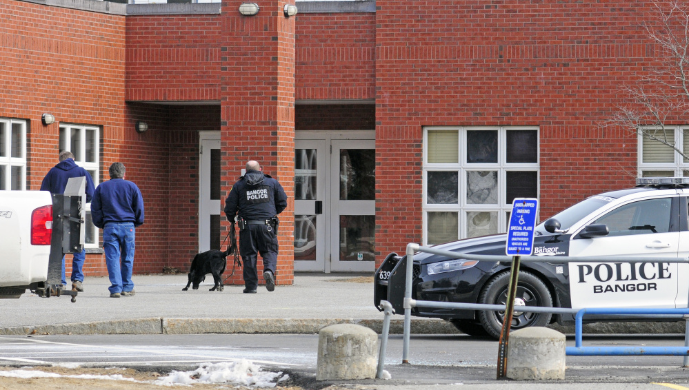 A Bangor police officer and a dog go into Farrington Elementary School during a search following a bomb threat on Friday that closed all Augusta public schools.