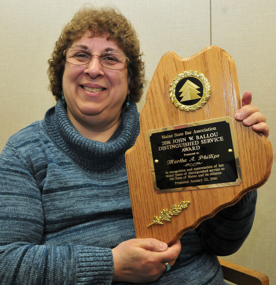 Martha Phillips on Wednesday holds the John W. Ballou award she received recently from the Maine Bar Association. Phillips volunteers to help people fill out court paperwork the first Wednesday of every month at Waterville District Court.