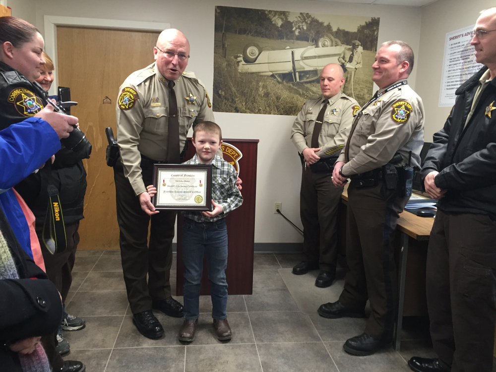 Franklin County Sheriff Scott Nichols gives Nicholas Rowe, 9, a Life Saving Certificate, Friday, for his role in helping save the live of trucker Charles Bolduc, who was shocked by electric wires on Rowe's grandparents' farm in New Vineyard in December. Rowe ran and got his uncle, who was recently certified in CPR, while Rowe's grandmother, Becky Lane, administered CPR.