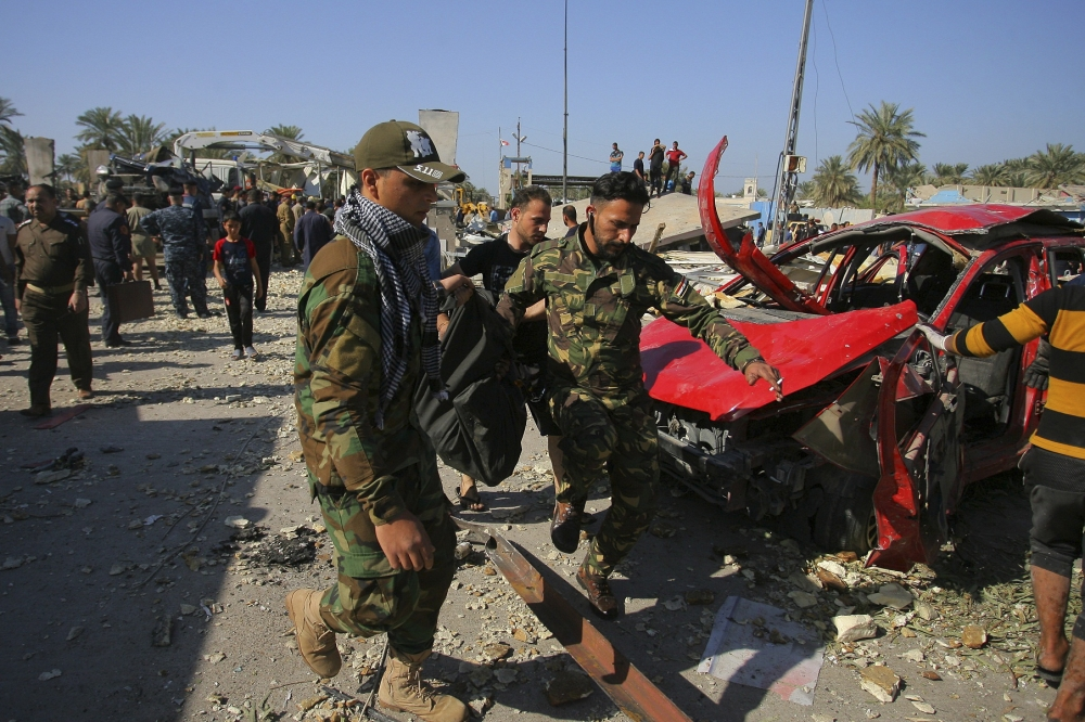 Security forces evacuate a victim's body after a bombing at a checkpoint crowded with cars and people in Hillah, Iraq.
