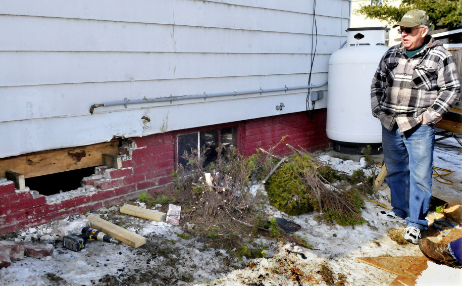 Homeowner Roland Hallee on Sunday looks over the damage to a basement wall on Green Street that was made when a woman crashed her car into the building on Saturday. The woman narrowly missed parked cars and the propane tank, background, before fleeing. She crashed again near Spring Street in Waterville and was arrested.