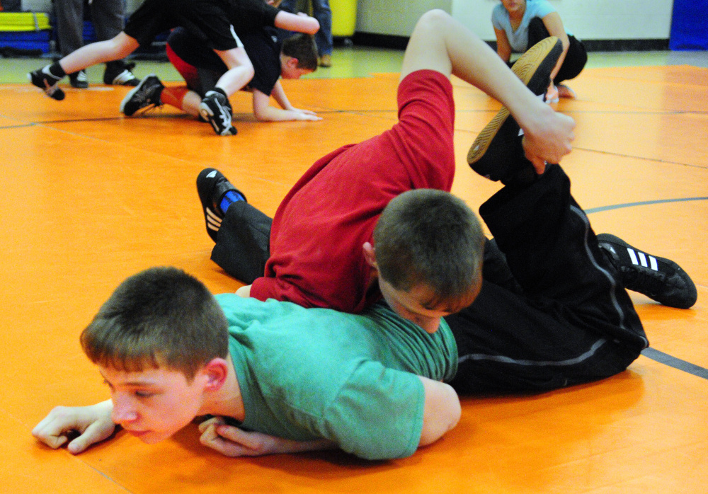 Devyn Purington, left in green, and twin brother Dana Purington do a drill during wrestling practice on Thursday at Gardiner Regional Middle School.