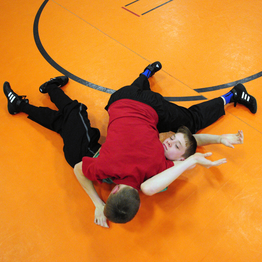 Dana Purington, top in red, and twin brother Devyn Purington do a drill during wrestling practice on Thursday at Gardiner Regional Middle School.