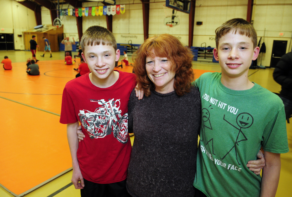 Mud In Your Face organizers Dana Purington, left, Penny McKinney and Devyn Purington pose for a photo during wrestling practice on Thursday at Gardiner Regional Middle School.