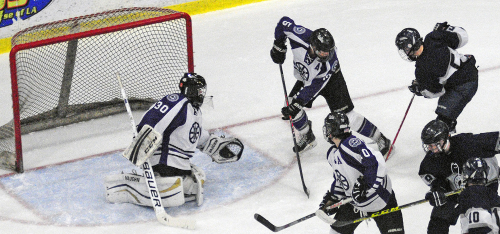 Waterville goalie Nathan Pinnette guards the net with defenseman Andrew Roderigue against Yarmouth during the Class B boys hockey state championship game Saturday at Androscoggin Bank Colisse in Lewiston.