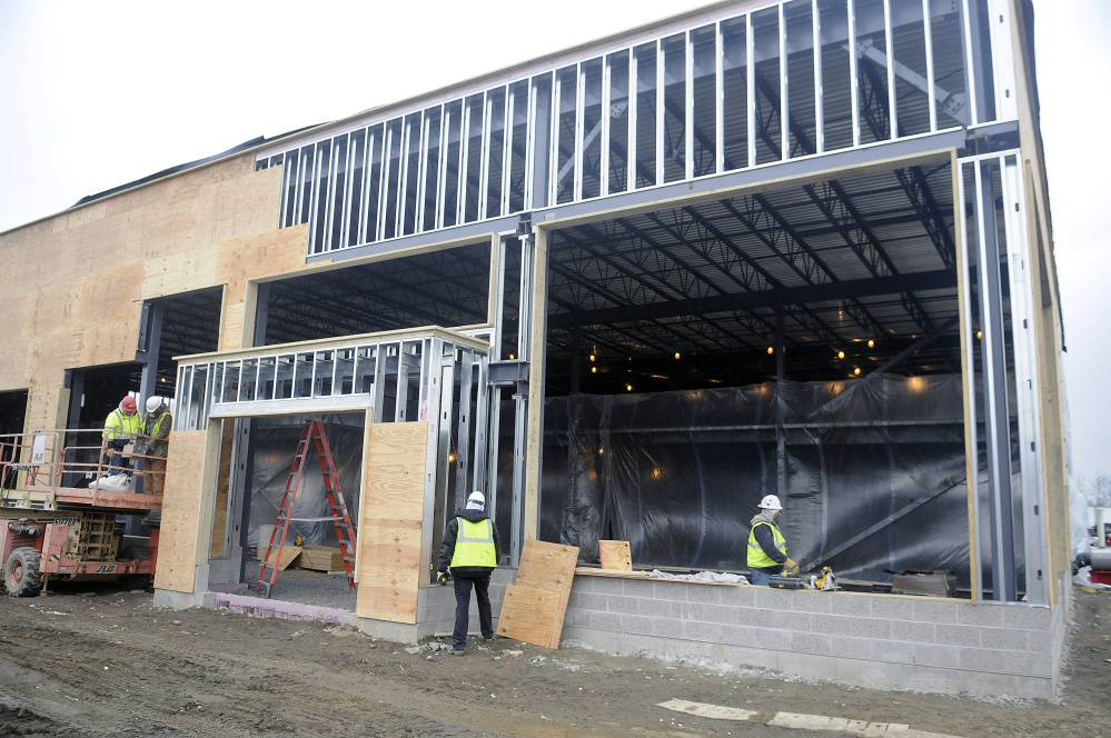Workers on Monday construct a new building for Darling's Auto Group at the corner of Old Winthrop Road and Western Avenue in Augusta to take the place of the car dealer's primary building at 439 Western Ave.