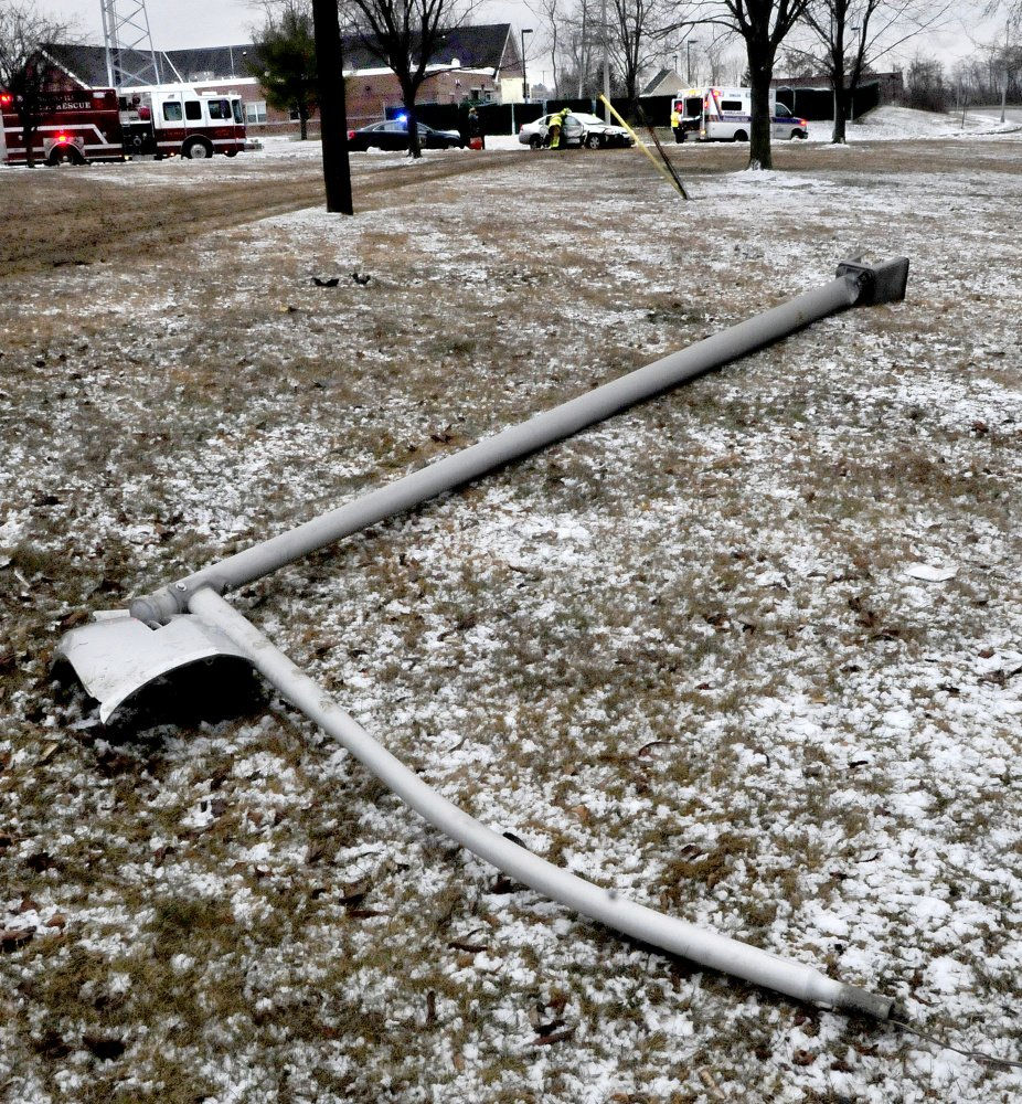 One of two light poles were knocked down by an out of control vehicle that slid off Front Street in Waterville on Monday.