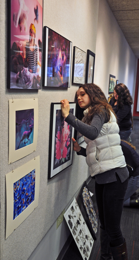 """Kents Hill School student Katie Sprague and a group of other area high school students hang works for the 10th Annual """"Higher Forms of Art"""" High School Art Exhibition last week in University of Maine at Augusta's Handley Hall in downtown Augusta."""
