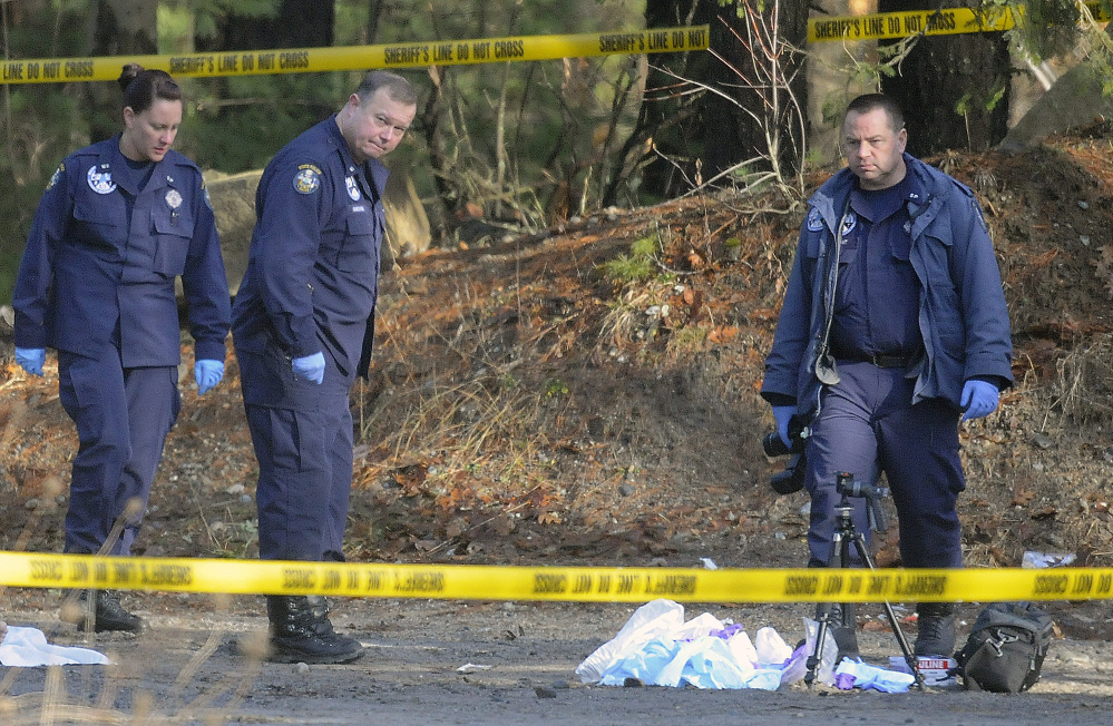 State Police detectives and evidence technicians examine where two bodies were discovered in an SUV on Sanford Road in Manchester early Christmas morning.