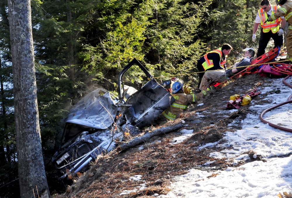 Firefighters pull an injured man strapped in a gurney up a steep embankment after he was removed from this vehicle that went off Route 135 in Belgrade on Tuesday.