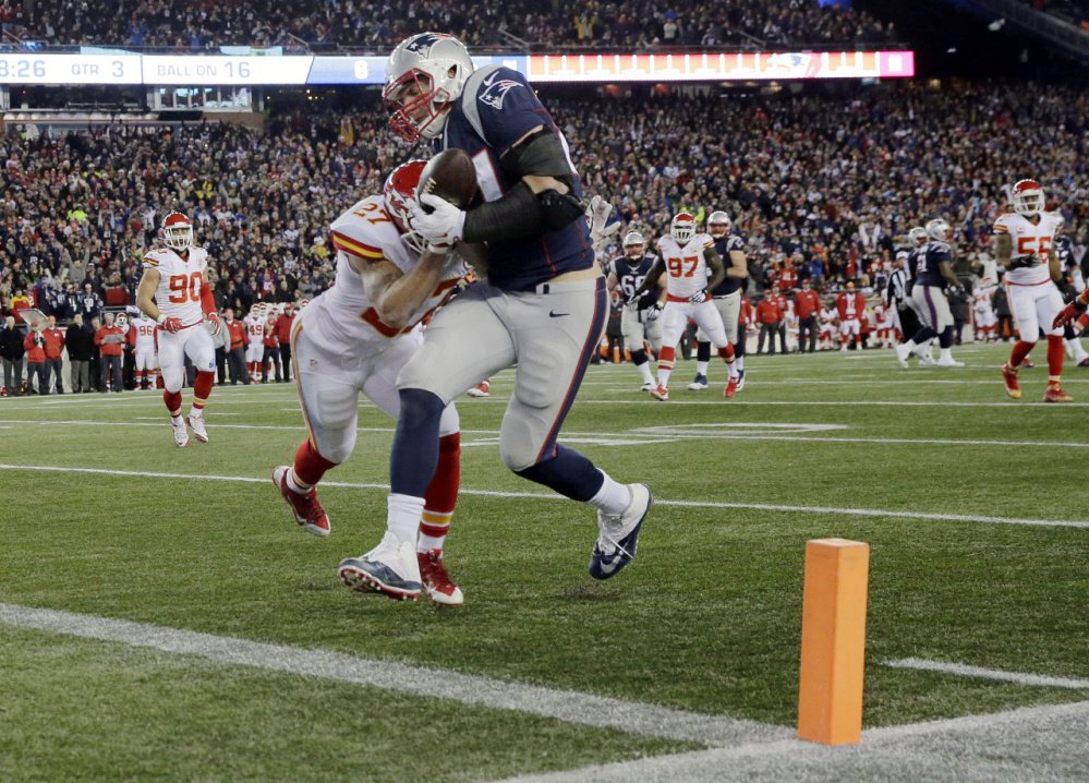 New England Patriots tight end Rob Gronkowski (87) catches a pass for a touchdown ahead of Kansas City Chiefs defensive back Tyvon Branch in the second half of an NFL divisional game Jan. 16 in Foxborough, Massachusetts. The Patriots reportedly picked up an option that will keep the Pro Bowl tight end in New England through 2019.