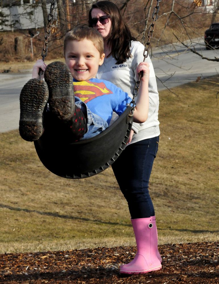 Abram Gallagher is all smiles as he gets a push on a swing  from Olivia White while enjoying a spring-like day at the Morton Brody playground in Waterville on Wednesday.
