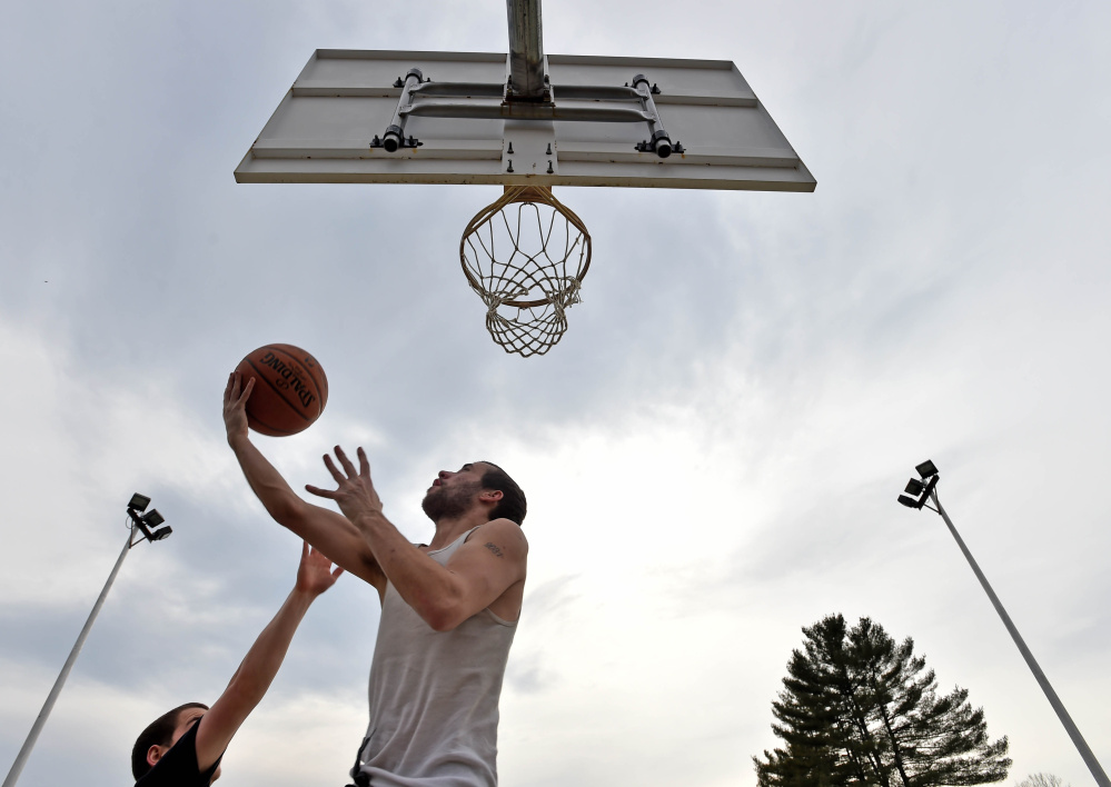 Mike Edwards, center, and Chris Senior, left, play a game of pick-up basketball at North Street Park in Waterville on Wednesday, where the temperatures hit the low 60s.