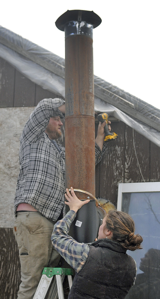 Alice Berry and Tom Stevenson hang a stovepipe from a greenhouse Wednesday at the Stevenson Farm in Wayne.  Seedlings started at Longfellow's Greenhouse in Manchester will be planted in the heated space this week, Stevenson said. Tomatoes should be available for sale at the farm's stand in Winthrop by June.