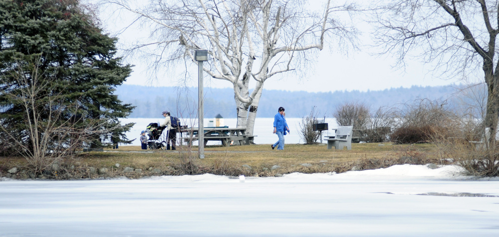 People walk around Norcross Point on Wednesday in Winthrop. There was some open water near the edges but Maranacook Lake was still mostly covered in ice.