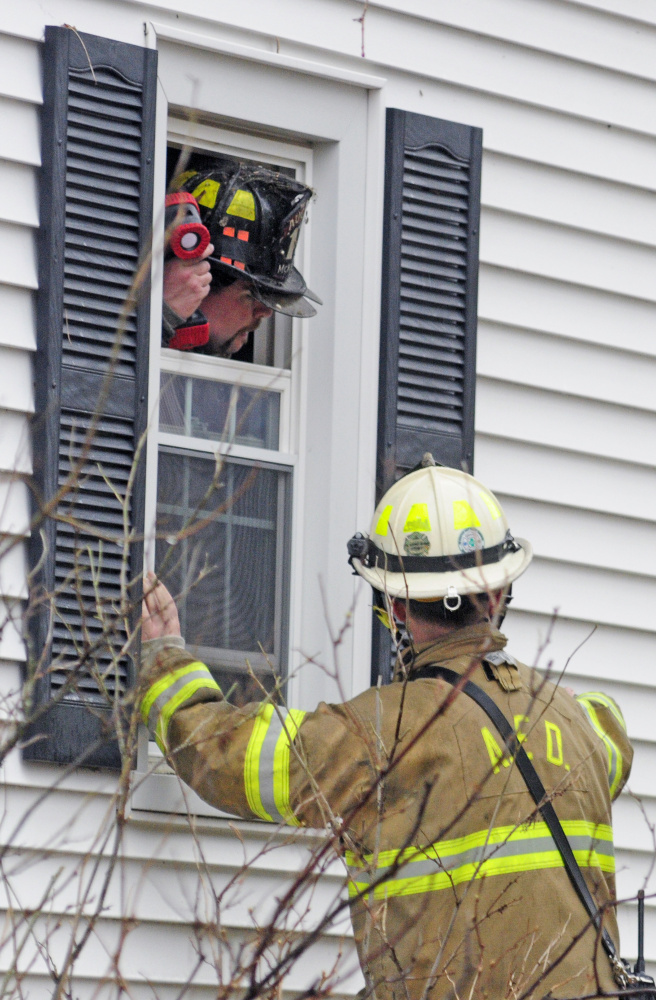 Augusta firefighters confer as several departments work at the scene of a house fire on Thursday at 65 Second St. in Hallowell.