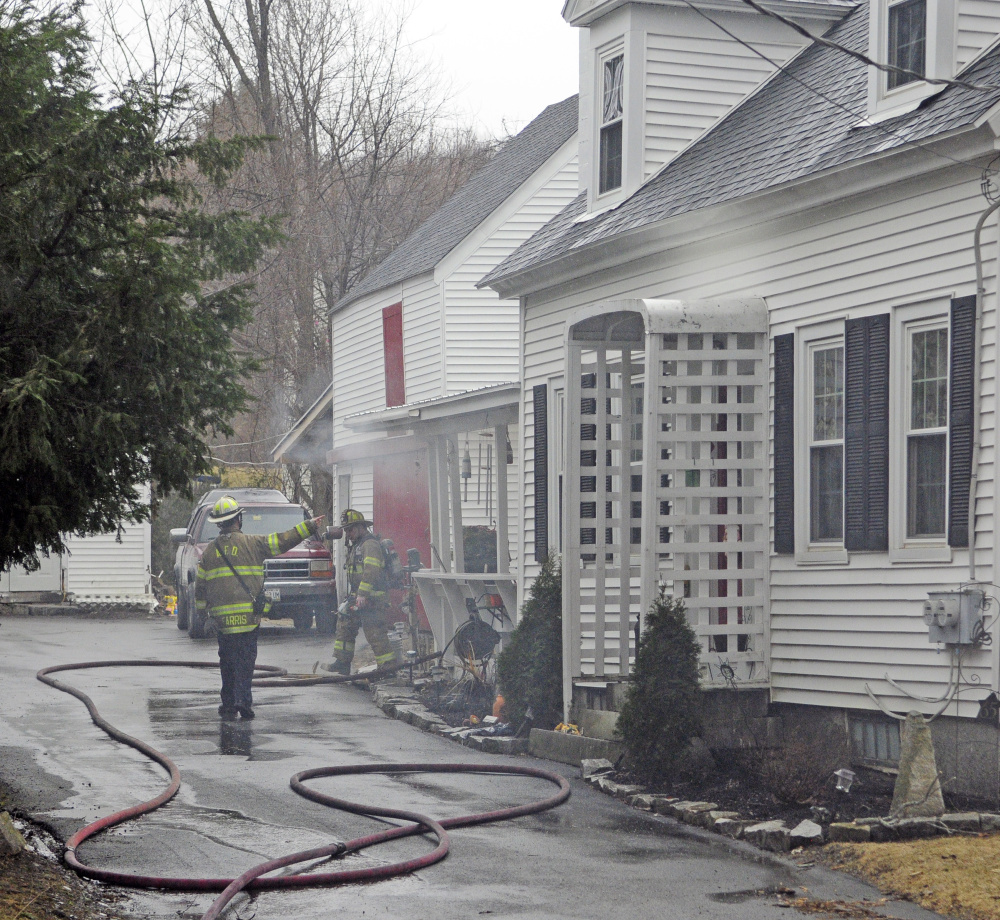 Smoke drifts from the building as firefighters from several area departments work at the scene during a house fire on Thursday at 65 Second St. in Hallowell.