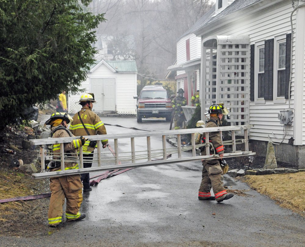 Smoke drifts from the building as firefighters from several departments work at the scene of a house fire on Thursday at 65 Second St. in Hallowell.