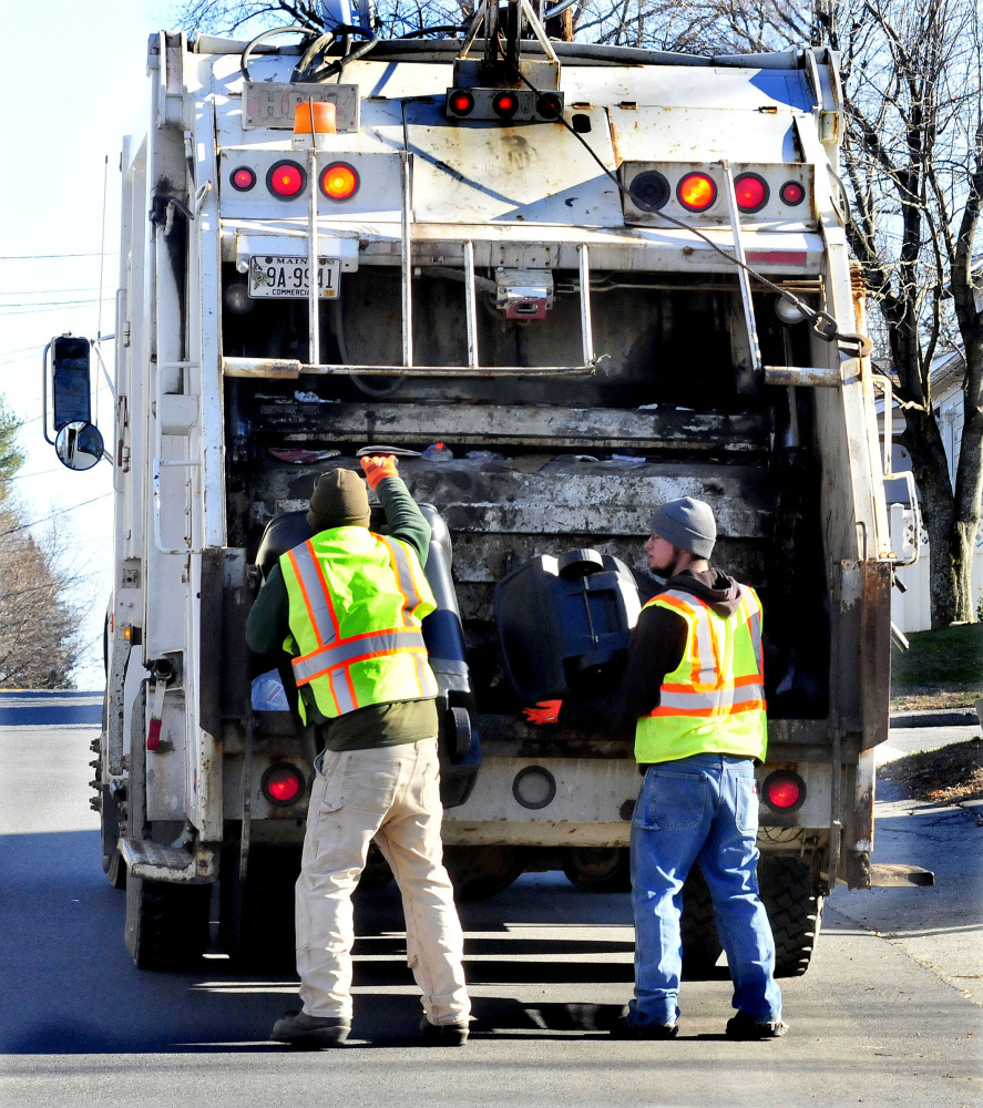 Winslow Public Works employees Josh Whitman, left, and Jacob Solomon fill a trash truck in November. The Town Council Monday will hear a proposal from Fiberight, which is looking to sign up towns for its Hampden biofuel plant that have PERC contracts that expire in 2018.