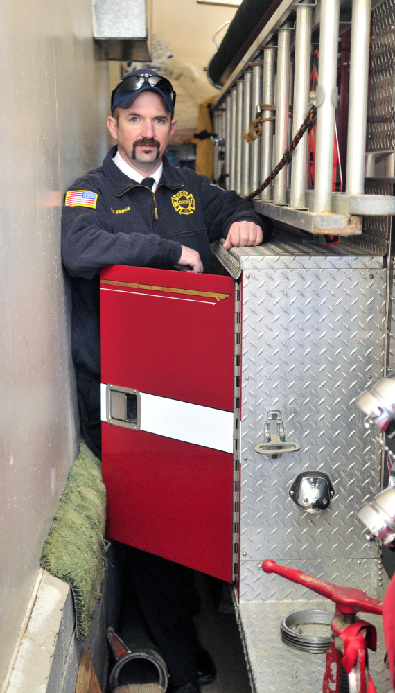 Staff photo by Joe Phelan Pittston Fire Chief Jason Farris demonstrates on Saturday that the storage compartment doors on fire engines can't be opened inside the tight confines of the fire station in East Pittston village.