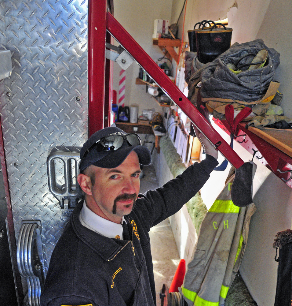 Pittston Fire Chief Jason Farris demonstrates on Saturday that the storage compartment doors on fire engines can't be opened inside the tight confines of the fire station in East Pittston village.