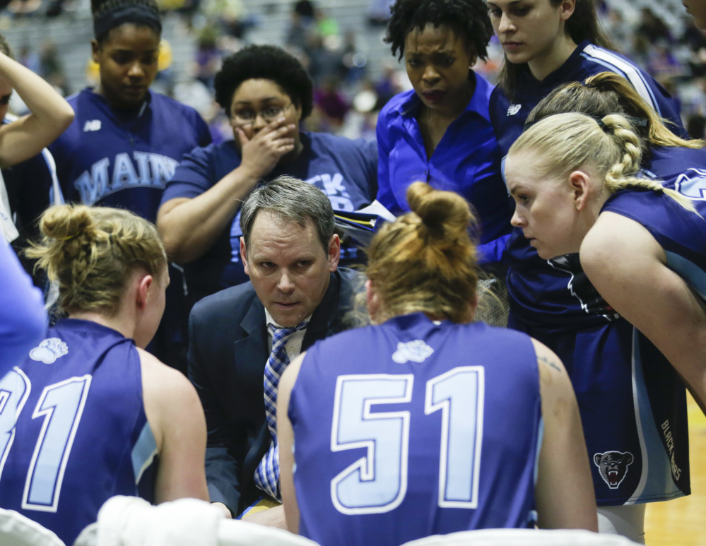 Maine head coach Richard Barron, center, talks to his players during a timeout during the second half an NCAA women's college basketball game against Albany in the America East Conference tournament championship on Friday in Albany, N.Y.