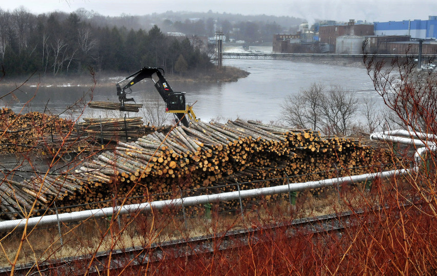 A worker unloads logs in a wood yard that will be used to make paper at the Madison Paper Industries mill in Madison, background, on Tuesday.
