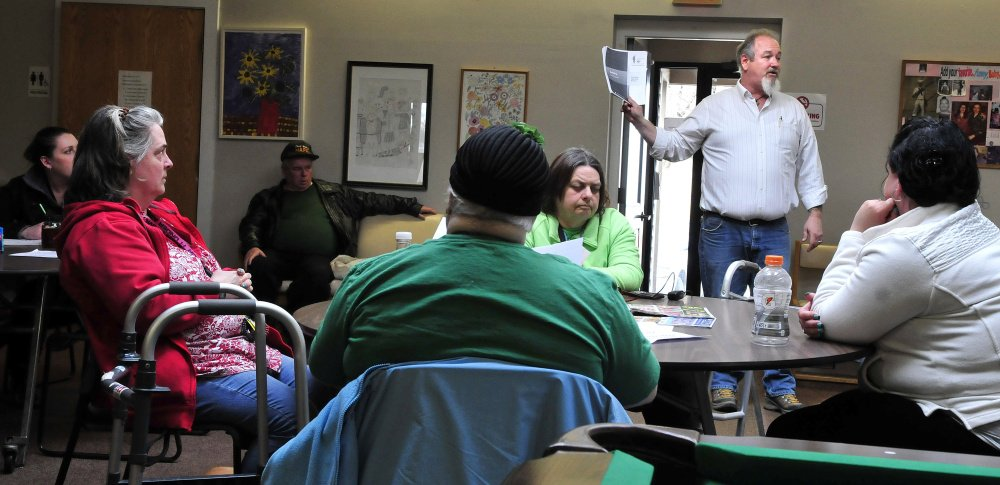 Troy Henderson holds of documents while explaining to members of the Waterville Social Club on Thursday that the peer-support center for people recovering from mental illness may close.