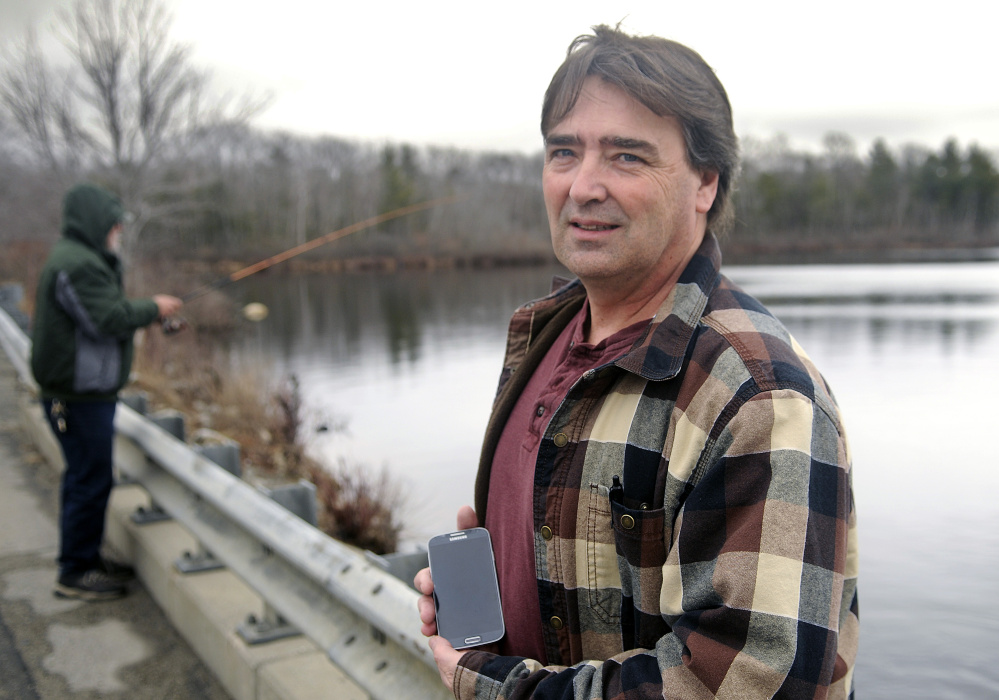West Gardiner resident Ron Cote, shown here last week at Togus Pond in Augusta, has developed an app for smartphones to help fishermen make sense of the state's rule book on fishing. Because it downloads a database to the phone, no cell service is needed to access the information.