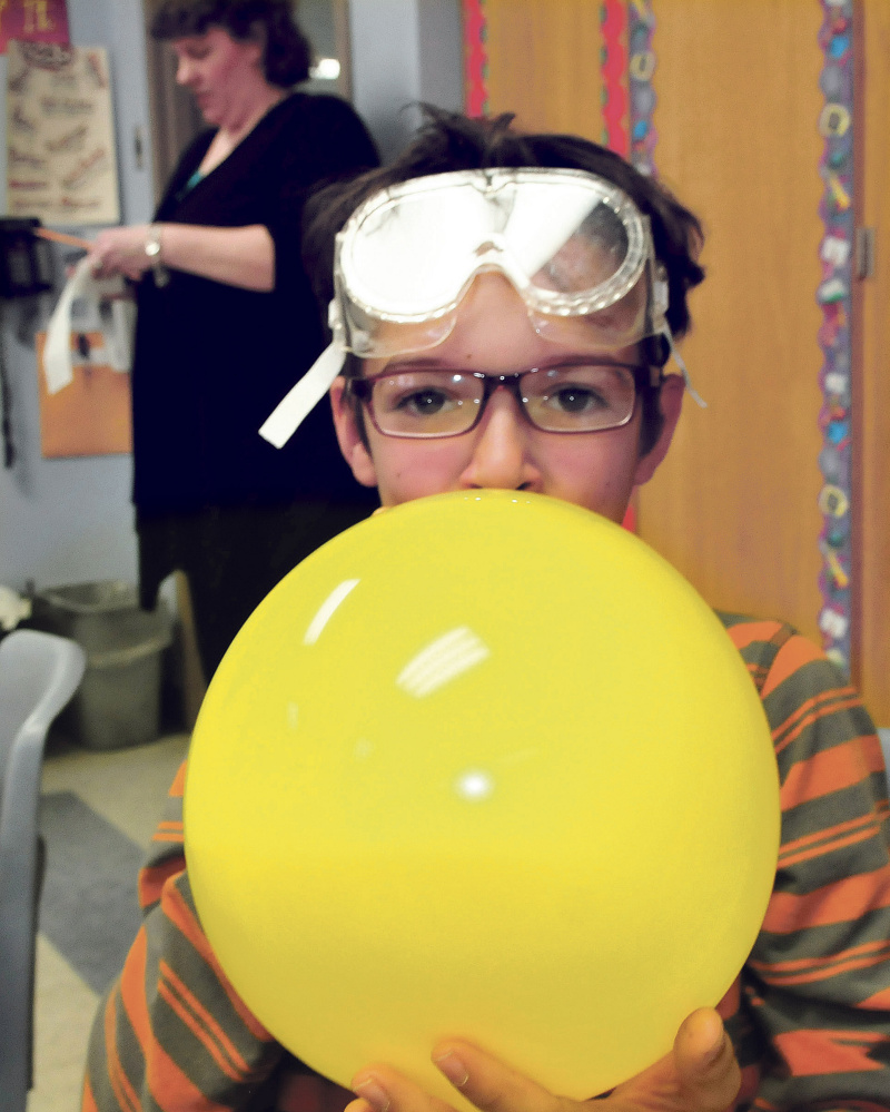 Cascade Brook School student Kyeden Thomas blows up a balloon used in a science project with University of Maine in Farmington students teaching the kids on Thursday. Behind Thomas is teacher Lynn Wells.