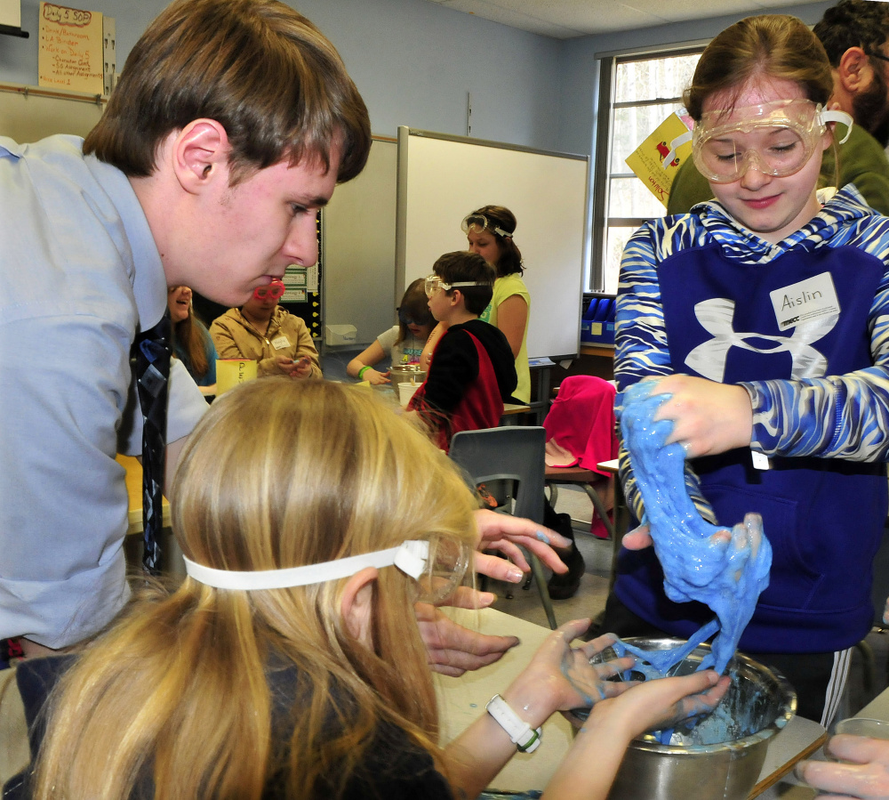 Cascade Brook School student Aislin Reynolds works with a gooey substance created by students under the direction of University of Maine in Farmington student Jacob Vining during a science project on Thursday.