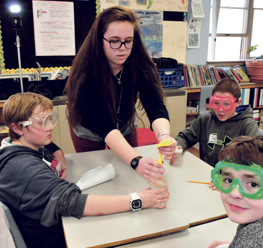 University of Maine in Farmington student Emily Gray works with Cascade Brook School students from left Jacob White, Caleb Norton and Marvin Gray on a science project on Thursday.