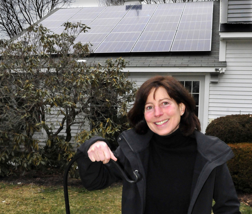 Jan King stands outside her home in Waterville on Thursday, where solar panels were recently installed on the roof as part of the Solarize Mid-Maine project.