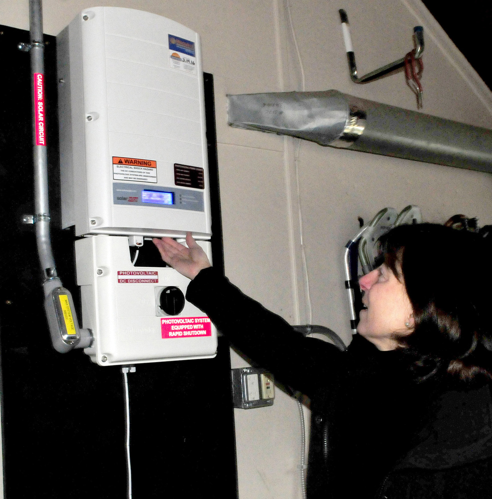 Jan King reads input numbers on an inverter that monitors electricity produced by solar panels on her home in Waterville on Thursday.