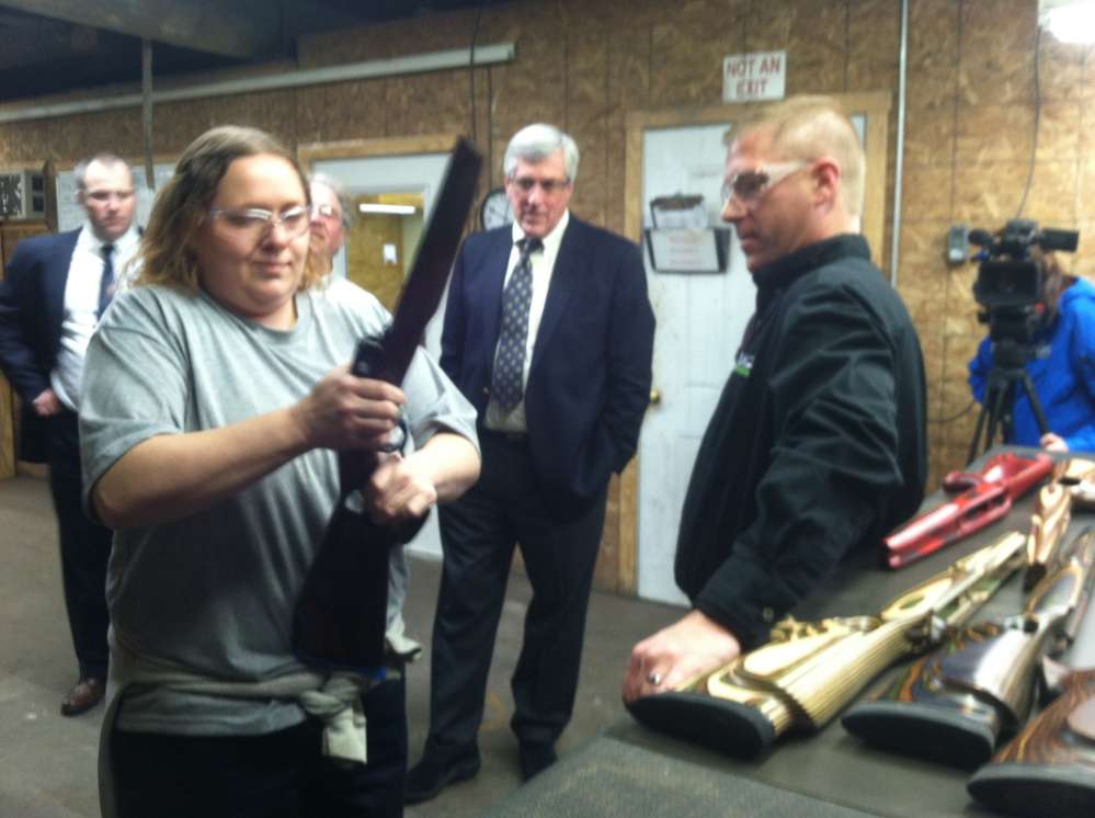 Alicia Lambert fits a rifle barrel into a wooden stock while Brody Cousineau, vice president of Cousineau Wood Products, looks on during a tour of the company's North Anson factory Friday.