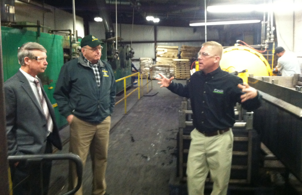 Brody Cousineau, right, explains the process Cousineau Wood Products uses to produce high-end wooden gun stocks during a tour of the company's North Anson factory Friday.