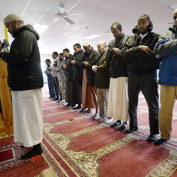 "Muslim men pray at the Maine Muslim Community Center. Leading the prayer to the left is imam Mohamed Abrahim, who says the term ""terrorist"" isn't applied equally when the perpetrators of violence aren't Muslim."
