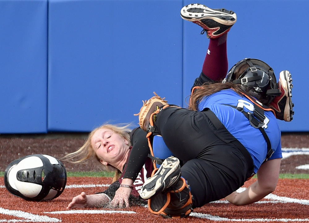 Colby College catcher Skylar Labbe, front, tags out University of Maine at Farmington runner Ashley Gleason at home plate during a non-conference game Wednesday in Waterville. The Mules swept a doubleheader in the first games on their new field.