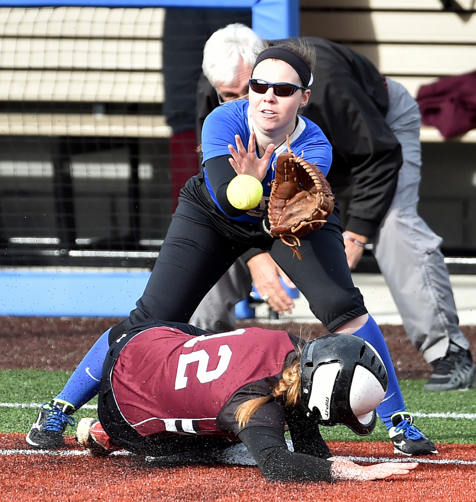 Colby College third baseman Paige Hartnett waits for the ball as University of Maine at Farmington runner Ashley Gleason slides safely into the bag during a non-conference game Wednesday in Waterville.